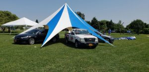A star pole tent with vehicles parked inside its archways