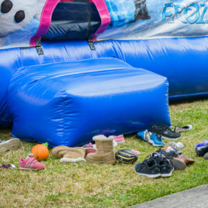 pairs of children's shoes stockpiled at the entrance way of a bounce house